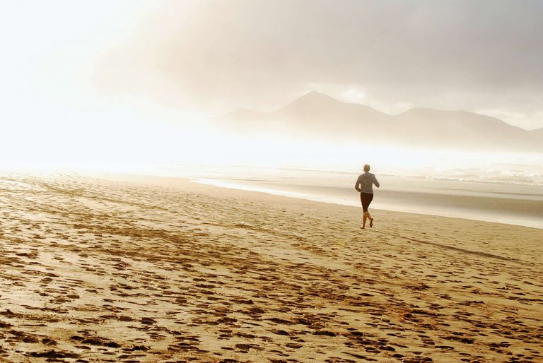 A woman is running on the beach